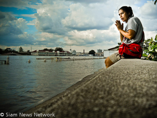 A women watches a flooded bank of the Chao Phraya River in Bangkok